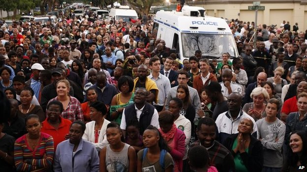 A group of people gather for a prayer service outside the home of former president Nelson Mandela