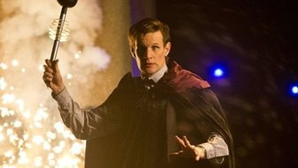 Matt Smith as the Doctor wields a Dalek's eye stalk above his head as an explosion goes off behind him