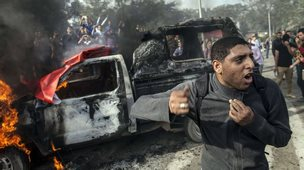 An Egyptian student at Cairo's University stands in front of a burning police vehicle