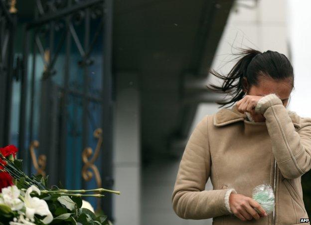 A woman weeps near a fence at Kazan airport, Russia, 18 November