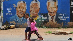 Children in Soweto walk past a Nelson Mandela mural