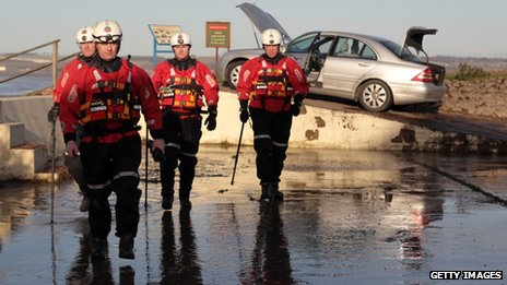 Humberside fire and rescue officers check a flood-damaged car blown on to the banks of the Humber Estuary flood defence wall