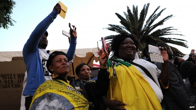 People take pictures with their cell phones as they pay a tribute to late former South African president Nelson Mandela outside his former house in Soweto on 6 December, 2013
