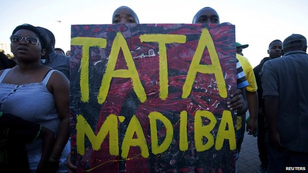 "People hold a poster reading ""Tata Madiba"" as they take part in an interfaith service for former President Nelson Mandela in Cape Town on 6 December, 2013"