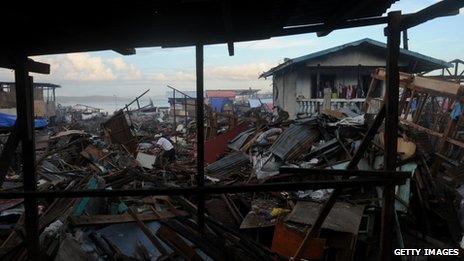 A man search for salavageable materials among debris of destroyed houses in Tacloban, Leyte province on December 6