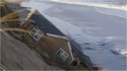 A home drawn into the sea during a tidal surge at Hemsby