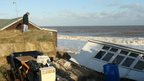 Man examines damaged property in Hemsby, Norfolk, on 6 December 2013