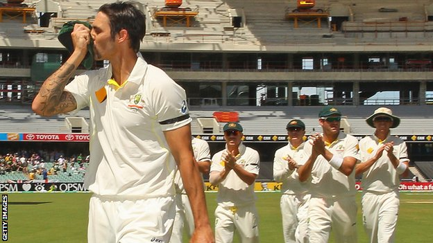 Mitchell Johnson kisses the badge on his cap as he leads Australia off at tea