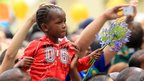 A girl carried by her father outside Nelson Mandela's old home in Soweto (7 Dec 2013)