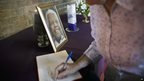Mourner signs book of condolence at Regina Mundi church in Soweto (7 Dec)