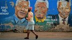 Woman walks past murals of Nelson Mandela in Soweto (7 Dec)