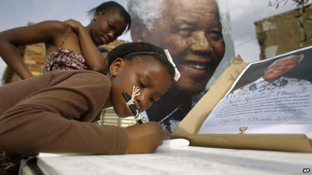 Two sisters sign a condolence book outside Nelson Mandela's first township home in Alexandra, Johannesburg