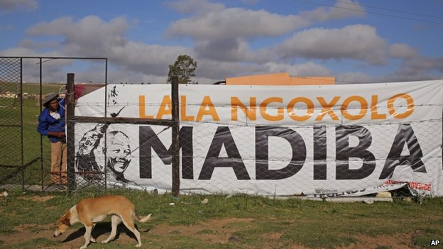 "In Qunu, where Mr Mandela will be buried, a banner was put up reading ""Rest in peace Madiba"""