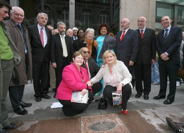 Former striker Mary Manning (in white jacket) next to a plaque commemorating the action of the Dunnes Stores workers in Dublin, 18 June 2008
