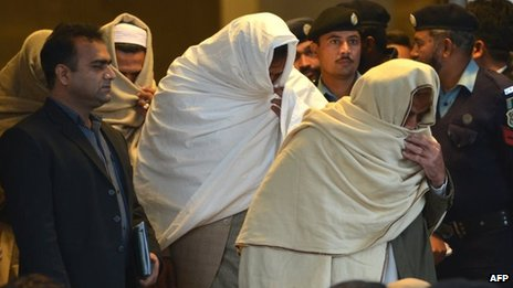 Pakistani policemen escort newly-identified missing persons as they leave the Supreme Court building in Islamabad