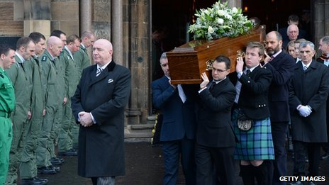 Coffin of Glasgow helicopter pilot David Traill being carried from church