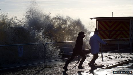 Two people run away from a wave hitting Lowestoft