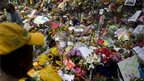 People look at flowers outside Mandela home in Houghton, S Africa (8 Dec 2013)