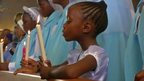 A child holds a lit candle at a memorial service for Nelson Mandela