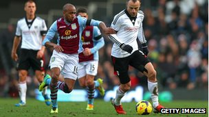 Dimitar Berbatov of Fulham is pursued by Fabian Delph of Aston Villa