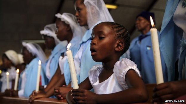 A child holds a candle during Sunday service on a national day of prayer for Nelson Mandela
