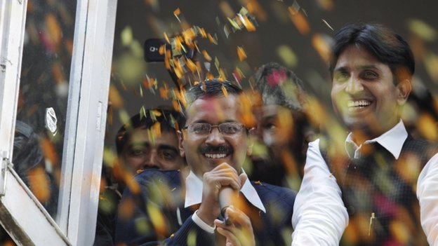 Supporters throw flower petals as Arvind Kejriwal, centre, leader of India's Aam Aadmi Party, or Common Man's Party, speaks as they celebrate the party's performance in Delhi state Assembly elections, in New Delhi, India, Sunday, Dec. 8, 2013.