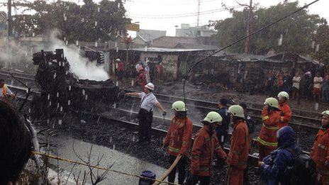 Firefighters are at the scene of the collision between a vehicle and a train in southern Jakarta, Indonesia, 9 December 2013