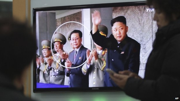 People watch a TV news programme showing an image of North Korean leader Kim Jong-un, right, and his uncle, Chang Song-thaek, third from left, at the Seoul Railway Station in Seoul, South Korea, 9 December 2013