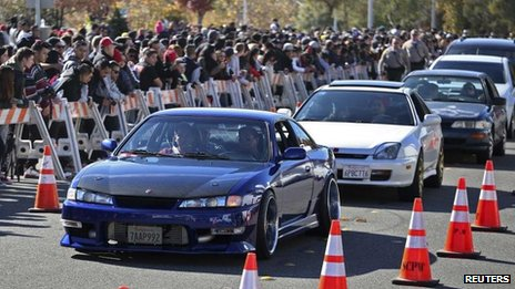Vehicles are driven past a crowd attending an unofficial memorial event for Fast & Furious star Paul Walker