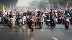 Anti-government protesters with Thai national flags ride their motorbikes as they rally on a main road in Bangkok