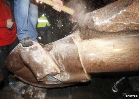 A man hits the Lenin statue with a sledgehammer