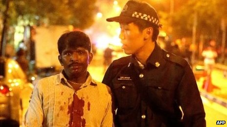 A South Asian man with a blood-spattered shirt is led away by a Singaporean policeman during the riot in Little India