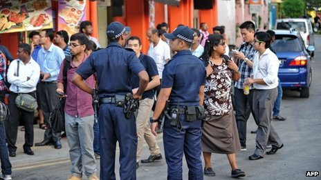 Policemen patrol in a street in Little India, the day after Sunday night's riot.