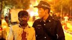 A South Asian man with a blood-spattered shirt is led away by a Singaporean policeman during the riot in Little India.