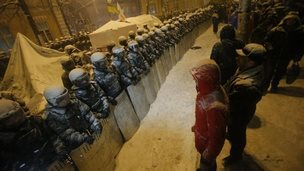 Ukrainian riot police face protesters outside government building in Kiev