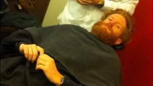 Sean Conway has his beard shaved off