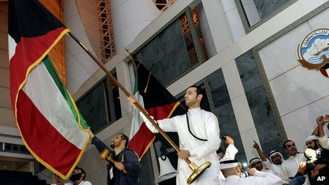Kuwaiti men wave flags after storming Kuwait's parliament building (16 Nov 2011)