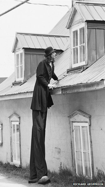 Gilles Ste Croix in stilts in front of house