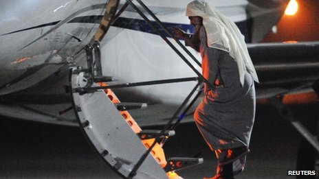 Abu Qatada walks up the steps onto a private jet