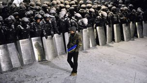 Protester walks past riot police near presidential offices in Kiev