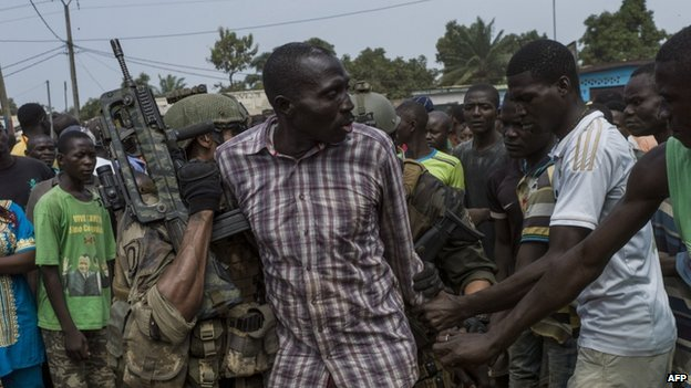 People gather around an alleged ex Seleka rebel arrested by French militaries in Bangui, on December 9, 2013