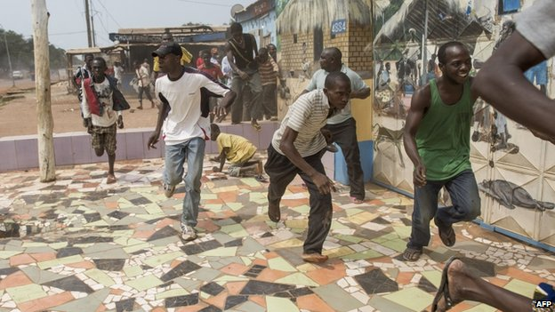 People run away from a gunfire during a disarmament operation by French soldiers in Bangui, on December 9, 2013