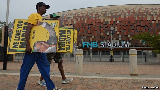 ANC members put up posters at FNB Stadium in preparation for Nelson Mandela's memorial service tomorrow, which will be attended by heads of state and up to 95,000 people, on December 9, 2013 in Johannesburg, South Africa