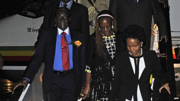 Zimbabwe's President Robert Mugabe and wife of Zimbabwe's President Grace Mugabe (C) arrive at Waterloo Airforce Base in Pretoria on December 9, 2013 to attend the memorial service of former South African President Nelson Mandela tomorrow