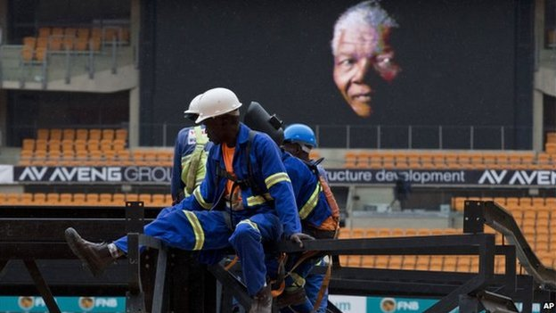 An image of former South Africa President Nelson Mandela is shown on a big screen as work is carried out to put up a stage at the FNB stadium where his memorial service will take place on Tuesday, in Johannesburg, South Africa, Monday, Dec 9, 2013