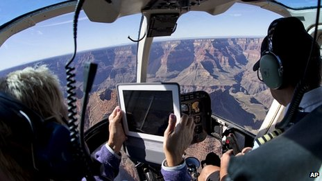 A tourist using a tablet computer to take a photograph during a helicopter tour of the grand canyon