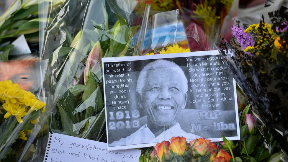Tributes and flowers are laid at the base of a statue of late former South African president Nelson Mandela in Parliament Square in central London on December 9, 2013.