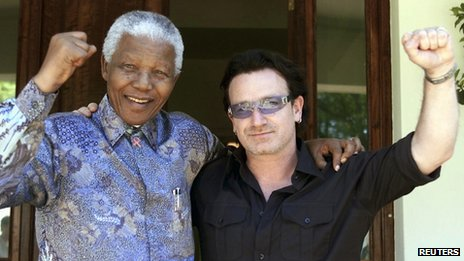 Former South African President Nelson Mandela (L) and Irish rock star Bono pose together after meeting at Mandela's residence at Houghton in Johannesburg, in this May 25, 2002 file photo