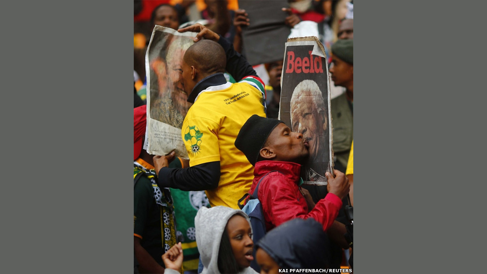 People kiss images of late former South African President Nelson Mandela