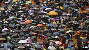 People holding umbrellas attend the memorial service for South African former President Nelson Mandela at the FNB Stadium in Johannesburg